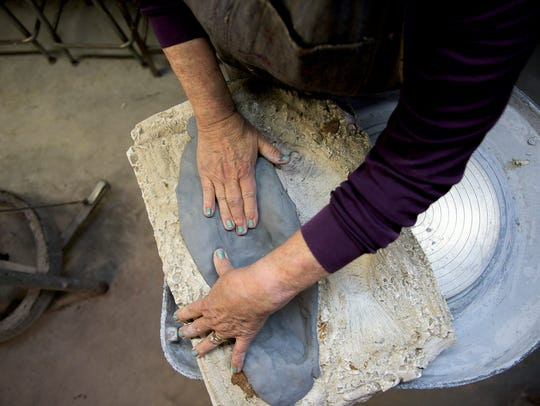 Nancy Mulick, 71, works on a clay fish inside the Barn