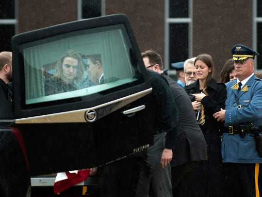 Jordan McCarson, second from right, watches as pallbearers place the casket of her late husband Eli McCarson into the hearse Wednesday, Dec. 23 at Rowan University in Glassboro.