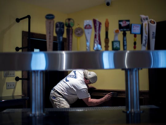 Rick Zemanik of Ricky Z Custom Painting stains woodwork behind the bar as the Double Eagle Saloon is rebuilt Thursday, Feb. 4 in Vineland. The establishment was destroyed after a fire May 6, 2014.