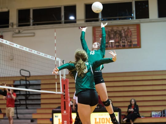 Lincoln setter Loren Scott (13) prepares to set up Kaylyn Buchanan for a kill during Saturday's Region 1-7A semifinal at Leon. The Lions won 3-1, sending the Trojans home after a strong season.