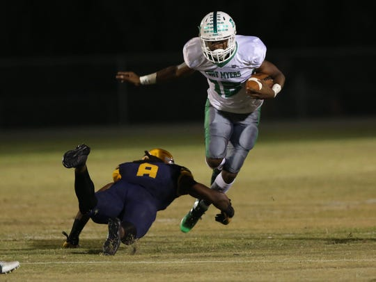 Fort Myers' Yasias Young tries to break the tackle of a Lehigh defender during a game earlier this season at Lehigh Senior High.