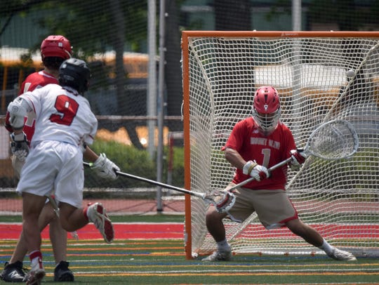 Mount Olive goalie Yanni Kalas can't stop ball shot by Northern Highlands #9 Joe Nirchio Boys lacrosse sectional final No. 1 Northern Highlands (white) vs. No. 3 Mount Olive (red)