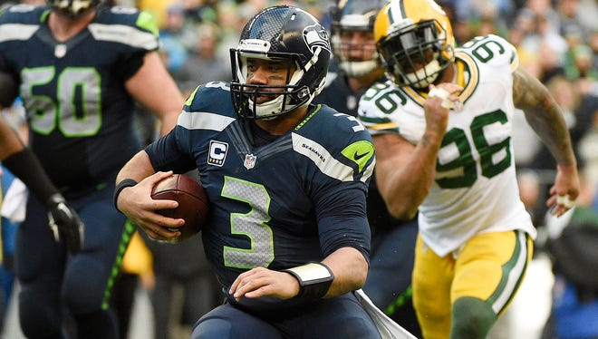 January 18, 2015; Seattle, WA, USA; Seattle Seahawks quarterback Russell Wilson (3) runs the ball against the Green Bay Packers during the second half in the NFC Championship game at CenturyLink Field.