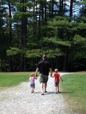 Officer Daryl Pierson walks with his niece, Madison, 3, and son, Christian, in Arrowhead Park, Inlet, NY in the Adirondacks on Aug. 30, four days before he died.