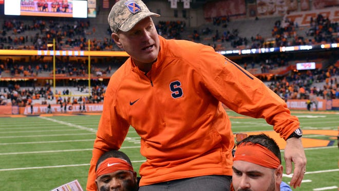 Scott Shafer gets carried off the field by two of his players after winning his final game 20-17 against Boston College on Saturday.