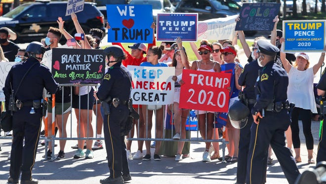Police watch as people gather at a barricade trying to get a look at the arrival of President Donald Trump during a fundraising trip in Dallas on Thursday.