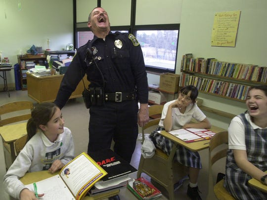 Chillicothe police officer Larry Cox shares a laugh with Bishop Flaget students in 2004. As the city police department D.A.R.E. officer, Cox's connection with local students was critical to his anti-drug message. Cox's death in 2005 left many of them inconsolable.