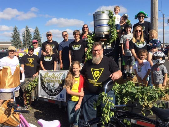 The Foothill Spargers Homebrewers pose with their float at the Homer Parade in 2017 at the annual Homer Davenport Community Festival. Their float is covered in fresh hops.