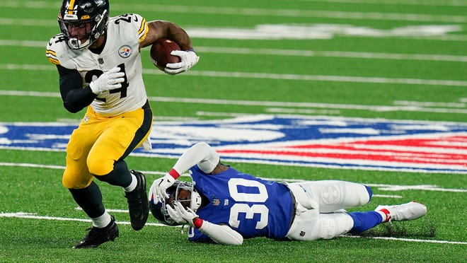 Steelers running back Benny Snell avoids a tackle by Giants cornerback Darnay Holmes during the first quarter Monday night.