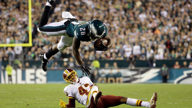 Eagles running back Wendell Smallwood (28) goes airborne while trying to avoid a tackle by Washington cornerback Quinton Dunbar during the first half on Monday night.