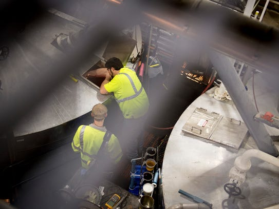 Workers check on the mash tanks at the George Dickel Distillery in Tullahoma, Tenn. The company struggled to pinpoint the source of chlorine that was showing up on water quality tests.
