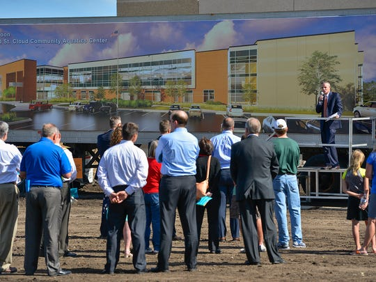 The crowd gathers to listen to Greg Gack, YMCA executive director, speak during a brief wall raising ceremony Tuesday, June 7, at the new St. Cloud Area YMCA Community & Aquatics Center site in Whitney Park. An artist's representation of the building is shown behind him.