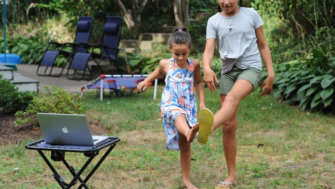Leah Hill, 5, and her sister, Peyton Hill, 10, dance to the Unicorn Song as they demonstrate how they use their computer for virtual square dancing Wednesday nights. Summer square dancing in Wellfleet, which has long been held at the town pier parking lot, has gone online this year due to the COVID-19 pandemic.
