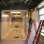 Browen Timothy installs ceiling panels on the second floor of School 12.  The school is scheduled to reopen next fall.