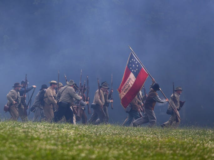 Re-enactors portraying Confederate soldiers in the Civil War demonstrate one of the first battles at Resaca, of the Atlanta Campaign, during the Heritage Village Museum's 2014 Civil War Weekend, on Sunday, July 13, at Sharon Woods Park.
