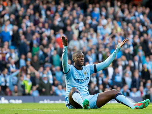 Manchester City's Yaya Toure appeals for a penalty unsuccessfully after being tackled by Manchester United's Marcos Rojo during their English Premier League soccer match at the Etihad Stadium, Manchester, England, Sunday Nov. 2, 2014. (AP Photo/Jon Super)