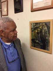 Fred Davis looks at a photograph of himself standing just behind Dr. Martin Luther King Jr. as they prepare to march for striking sanitation workers March 28, 1968, in Memphis.