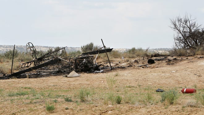 The charred skeleton of a single-engine plane is seen at the scene of a plane crash that killed pilot Michael Arnold at the Aztec Airport on May 18, 2013.