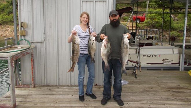 Sean Reynolds (right) and his girlfriend, Meridith, show off the stripers they caught on a family fishing trip Sunday.