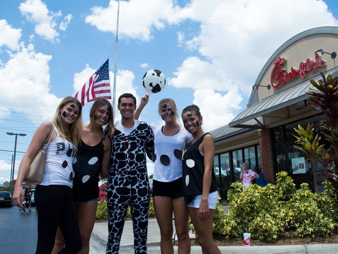 Locals dressed as cows corral themselves in the Chick-fil-A