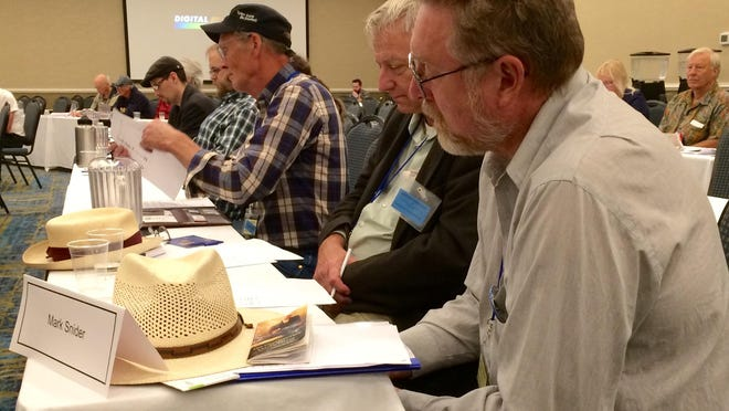 Mark Snider, James Olsen and Daniel Hutchinson review a list of candidates wanting to be Bernie Sanders delegates at the Democratic National Convention.