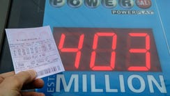 A Powerball quick-pick ticket is pictured near a sign
