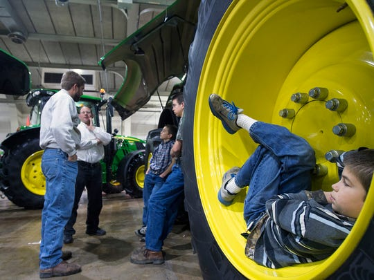 Taking a break from some adult talk, Brandon Hollinger gets comfortable inside the large wheel of a John Deere chopper. It's hard to find candid moments at trade shows. It's rewarding to find good moments in the flow of day to day events.