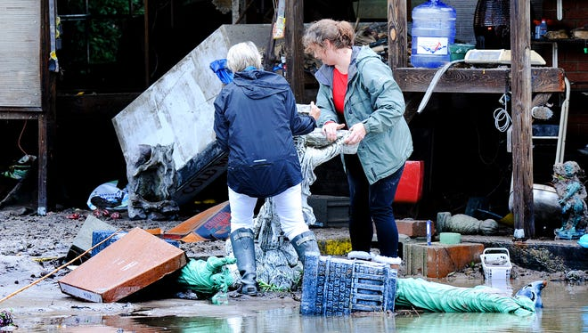 From left, Collins McDougall, sister of Forest Lake Gardens owner Joseph McDougall, and Sandy Roberts, a customer of the store help pick up after a massive flood on October 5, 2015.