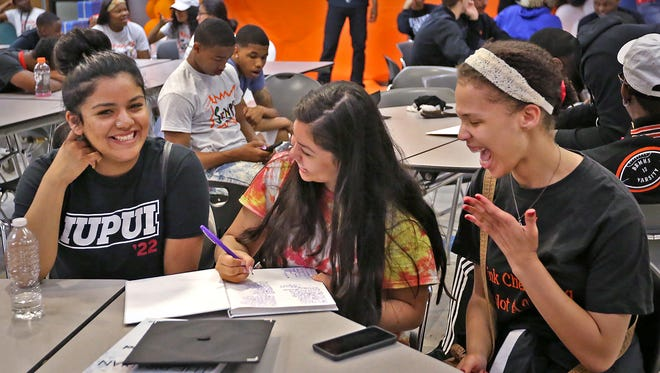 Friends Alejandra Varo from left, Jennifer Argumedo, and Marrissa Robertson sign yearbooks and enjoy a laugh as they wait for graduation practice on the last day of school at Broad Ripple High School, Thursday, June 7, 2018.  The school is closing, with this being the last graduating class.