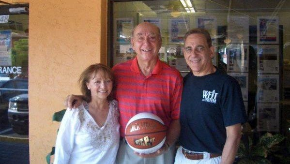 From left, Nohra Farber, Dick Vitale holding an autographed basketball, and Phil Farber.