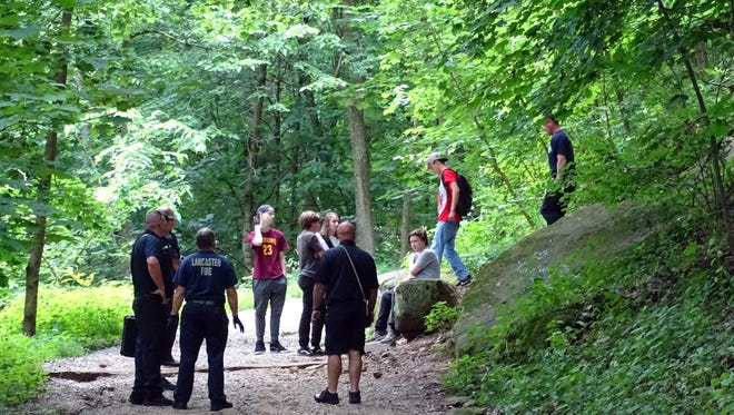 Lancaster firefighters help a 15 year-old boy back onto the trail up Mount Pleasant Saturday afternoon, July 15, 2017, at Rising Park in Lancaster. According to Lancaster Fire Department Lt. K.J. Watts the boy and his friends had been off the marked trail throwing rocks at one another when he was struck by a rock and fell about 10 feet. Watts said the boy was briefly unconscious, but was able to walk down the hill to a waiting ambulance. He was taken to Fairfield Medical Center for treatment.