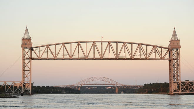 The sunset reflects off the Railroad Bridge and Bourne Bridge in this file photo.