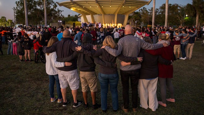Family, friends and community members embrace during a religious vigil at Pine Trails Park in Parkland, Fla., on Wednesday, March 14, 2018.