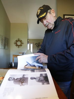Vietnam War veteran and three-time Purple Heart recipient Tom Scherg looks through a book of photos taken of him while he served in the Marines.