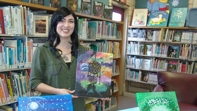 Alyssa Hostetler poses with some of her acrylic paintings that will be on display at the West Lafayette Branch Library throughout January.