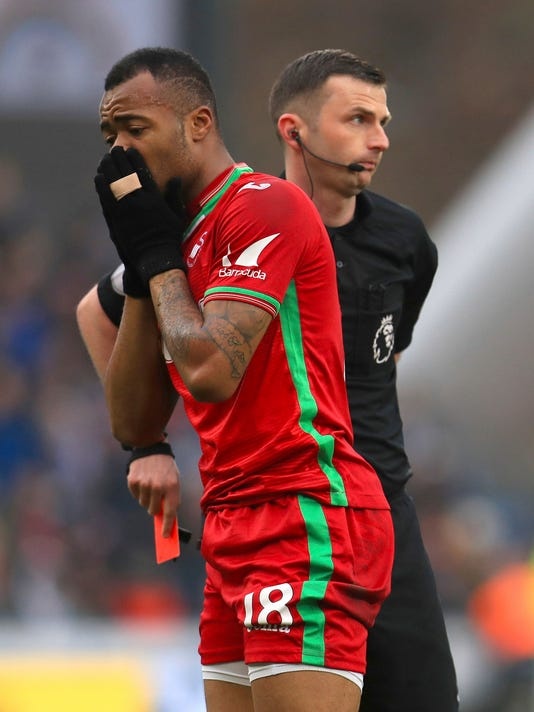 Swansea City's Jordan Ayew reacts after being shown the red card by referee Michael Oliver during the game against Huddersfield Town during their English Premier League soccer match at the John Smith's Stadium in Huddersfield, England, Saturday March 10, 2018. (Mike Egerton/PA via AP)