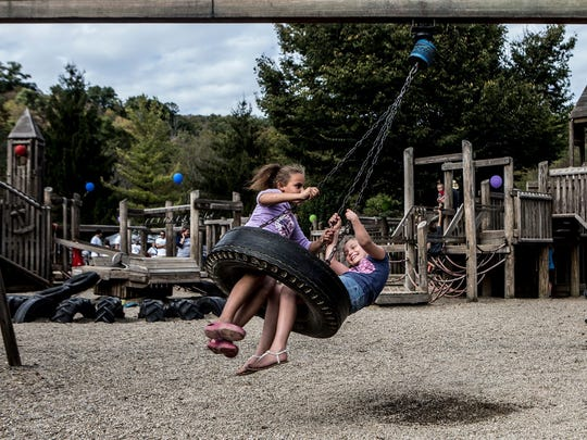Savannah Woody and Maygen play on the tire swing at Wildwood park in Granville during the last chance play day.
