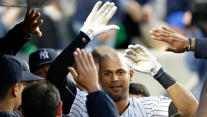 Teammates congratulate New York Yankees Aaron Hicks, center, after Hicks hit a third-inning, solo, home run in a baseball game against the Kansas City Royals at Yankee Stadium in New York, Monday, May 9, 2016.  (AP Photo/Kathy Willens)