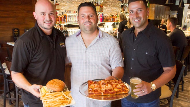From left, Sean Azzo and brothers Mike and Patrick Jonna celebrate the opening of Jonna's Bar & Grill Tuesday, Aug. 1, 2017 in Howell Township. Sean holds a burger with the restaurant's signature sauce, Mike holds a deep dish personal pizza and Patrick holds a glass of Witch's Hat Kolsh-style beer.