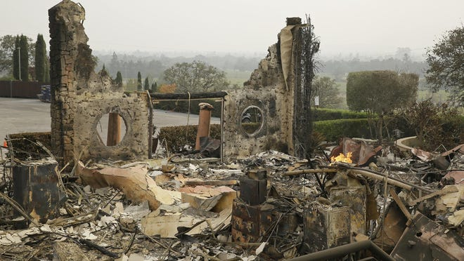 In this Oct. 10, 2017 file photo, the remains of the Signorello Estate winery continue to smolder in Napa, Calif.