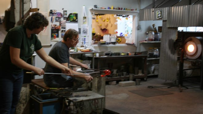 Robert Kuster and Kelly Moyers finish a glasswork.
