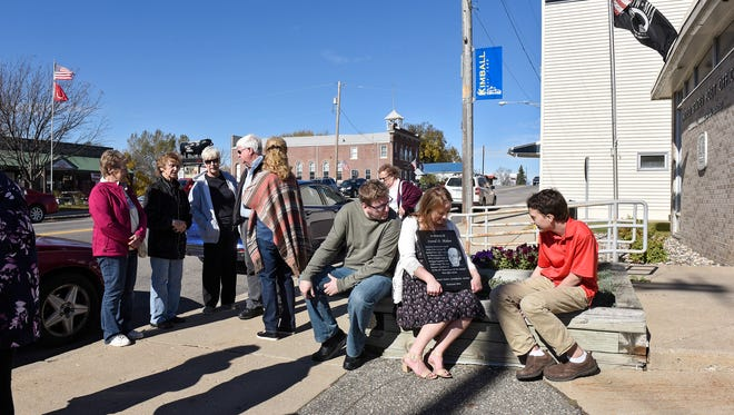 People view a plaque in memory of Kimball assistant postmaster Ivend Holen during a dedication ceremony Tuesday, Oct. 18, in front of the Kimball Post Office. Holden was killed by a bomb while working at the post office in 1976. The case has not been solved.