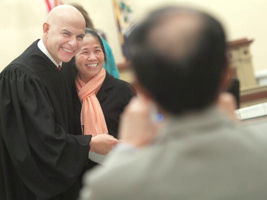 Kieu Nguyet Thi Nguyen, from Vietnam, poses for a picture with Judge Flannelly during the Naturalization ceremony held at the York County Administrative Center on Thursday, March 28, 2013.  YORK DAILY RECORD/SUNDAY NEWS--JASON PLOTKIN