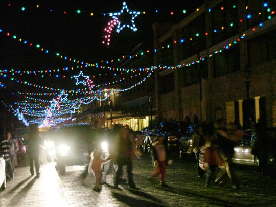 Christmas festival-goers cross Front Street in Natchitoches.