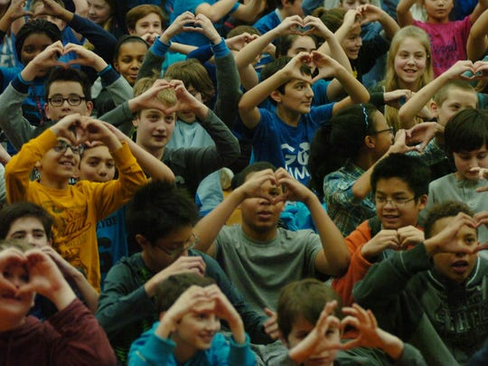 Berkshire Middle School students show their support by making heart-like shapes with their hands.
