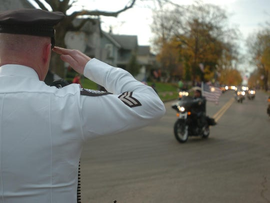 An officer salutes as the funeral procession for U.S. Navy Builder Chief Petty Officer Raymond Border turns from Main Street in West Lafayette onto Ohio 93 to Plainfield Cemetery.