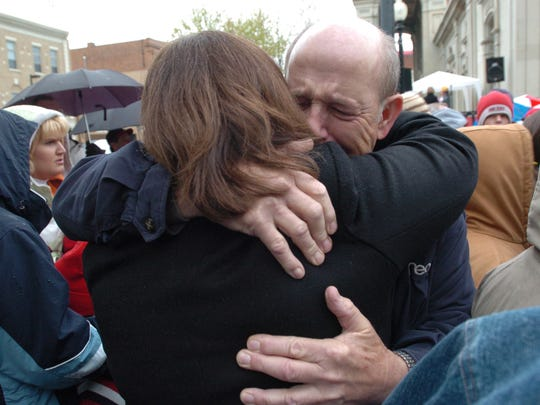 Randy Cox, uncle of Chillicothe police officer Larry Cox, hugs another person at a candlelight vigil conducted days after Cox's fatal shooting in April 2005. Hundreds of people gathered outside the Ross County Law Enforcement Complex to mourn the loss of the popular officer.