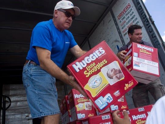 Volunteers Jim Luther, left, and Chad Thomas help unload a truck load of Huggies diapers to the Destiny Diaper Bank in Fort Myers. State Senator Lauren Book wants to exempt diapers and other incontinence products from the state sales tax.