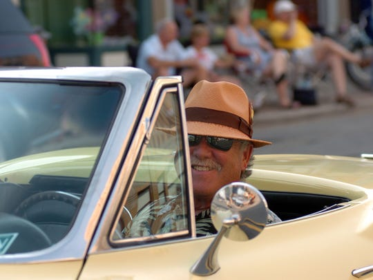 Michael Berro, of Port Huron smiles from behind the wheel of his 1967 yellow Corvette Stingray as he makes his way down Huron Avenue on July 6, 2012, during the 2012 Blue Water Open Cruise.