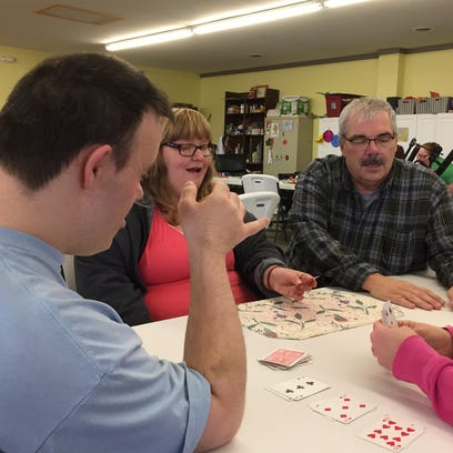 Kenny Little, right, plays a game of cards with clients